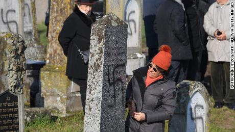 People look at tombs at Westhoffen cemetery near Strasbourg after they were desecrated.