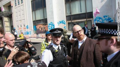 Police arresting Simon Bramwell for super gluing himself to the Shell Centre in London in April.