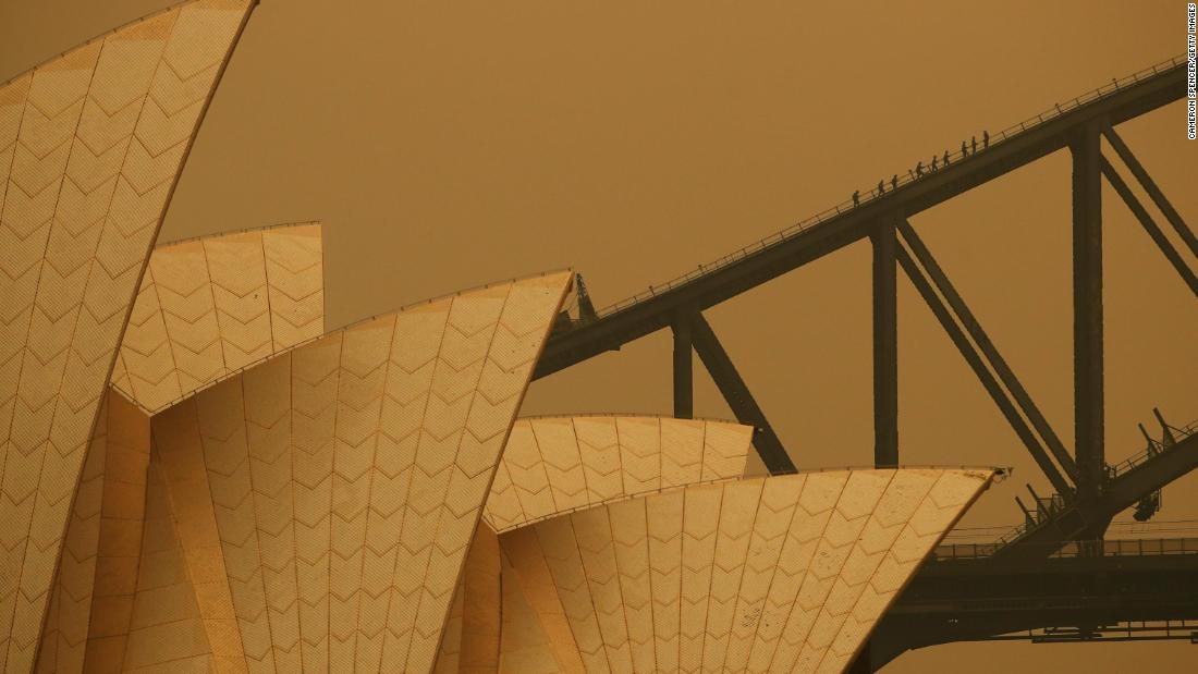 People join a guided climb of the Sydney Harbour Bridge as bushfire haze darkens the sky on December 6.