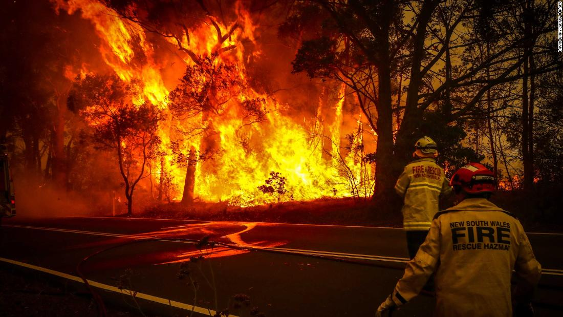 Fire and rescue personnel monitor a bushfire as it burns near homes on the outskirts of Bilpin on Thursday, 十二月 19.