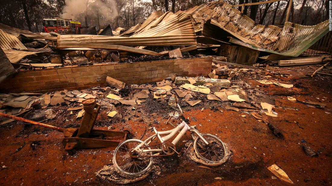 A charred bicycle lies on the ground in front of a house destroyed by bushfires on the outskirts of Bargo on December 21.