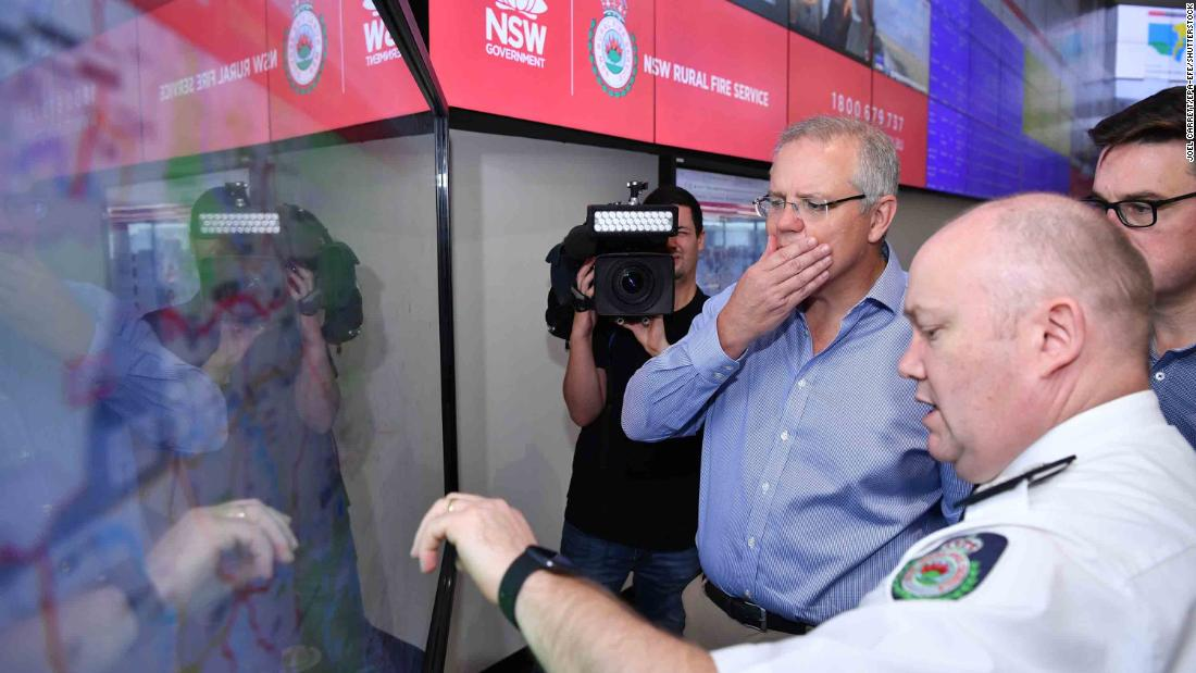 "Australian Prime Minister Scott Morrison is briefed by fire officials at New South Wales Rural Fire Service control room in Sydney on December 22. Morrison arrived back in Sydney <a href=""https://edition.cnn.com/2019/12/22/asia/australia-fire-prime-minister-criticism-apology/index.html"" 目标=""_空白&amp报价t;>amid criticism after taking a family holiday to Hawaii during the bushfire emergency.</一个>"