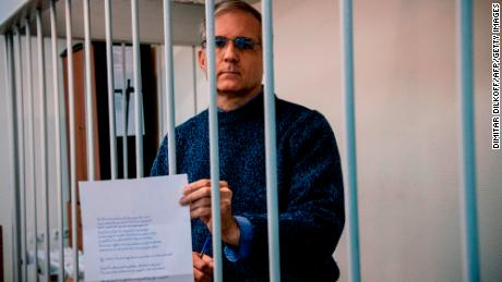 Paul Whelan, a former US Marine accused of espionage and arrested in Russia in December 2018, holds a message as he stands inside a defendants' cage before a hearing in October 2019.