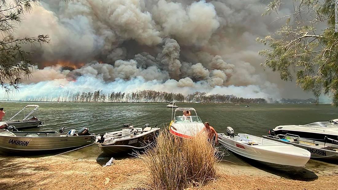 Boats are pulled ashore as smoke and wildfires rage on January 2 behind Lake Conjola.