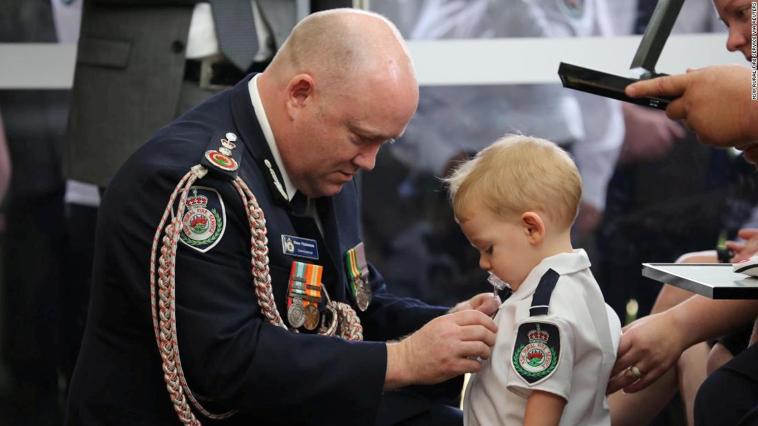 "Royal Fire Service Commissioner Shane Fitzsimmons presents a posthumous Commendation for Bravery and Service on January 2 to the son of RFS volunteer Geoffrey Keaton, 谁是 <a href=""https://edition.cnn.com/2020/01/02/australia/australia-medal-firefighter-son-intl-scli/index.html"" 目标=""_空白&amp报价t;>killed battling bushfires</一个>, at Keaton's funeral in Buxton, New South Wales."