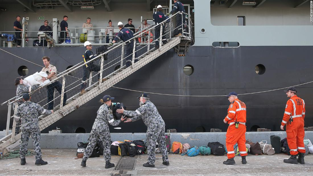 A Royal Australian Navy crew unload luggage as evacuees from Mallacoota arrive aboard the MV Sycamore on January 4 at the port of Hastings, 澳大利亚.