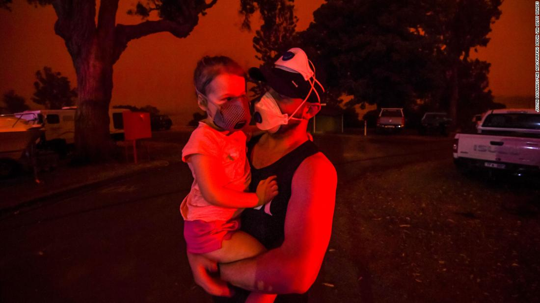 A father holds his daughter as the skies above turn red during the day on January 4 in Mallacoota, 澳大利亚. Many parents with young children were stuck in Mallacoota after flights were grounded because of smoke and only school-aged children and older were allowed to evacuate by boat.