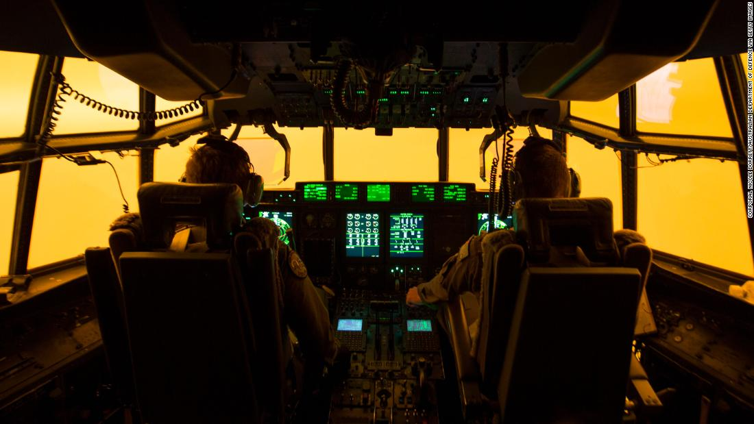 The flight deck of a C-130J Hercules is lit by the red glow of the fires below as the aircrew attempts to land in Merimbula to drop off fire and rescue crews to assist fighting the bushfires on January 5.