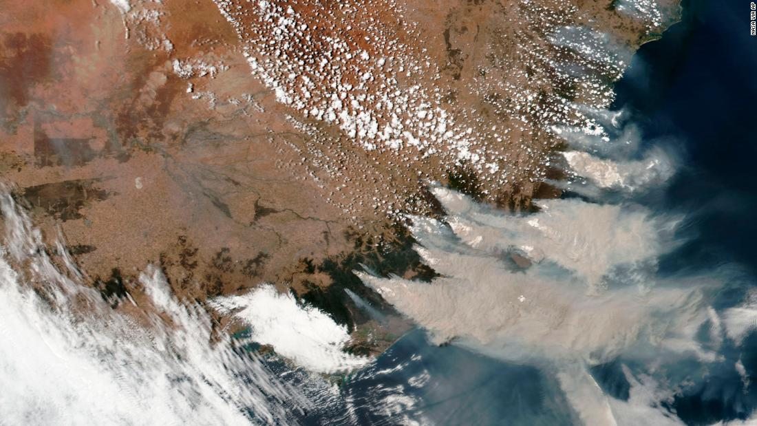 This satellite image provided by NASA on Saturday, 一月 4, shows smoke from fires burning in Victoria and New South Wales.