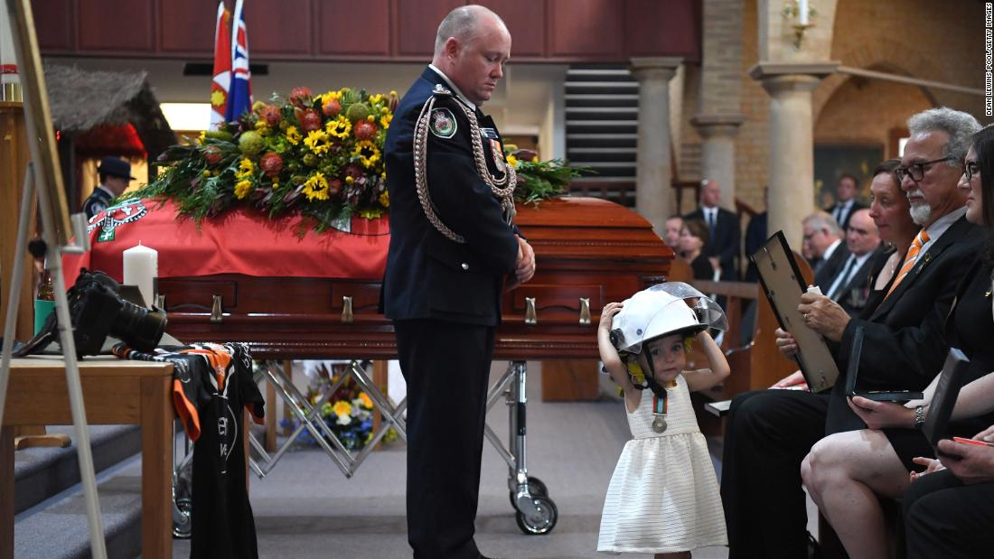 Charlotte O'Dwyer, the young daughter of Rural Fire Service volunteer Andrew O'Dwyer, wears her father's helmet during his funeral after being presented with a service medal in his honor by RFS Commissioner Shane Fitzsimmons on Tuesday, 一月 7, in Sydney.