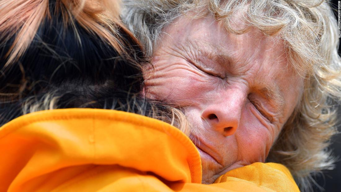 Stephenie Bailey is embraced on Wednesday, 一月 8, as she describes the impact the bushfires have had on her farm in Batlow.
