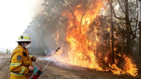 A firefighters backs away from the flames after lighting a controlled burn near Tomerong, Australia.