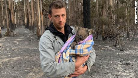Jack Bruce holds Wilbur, a koala rescued from the fires, who he and his partner Alyex Burges are helping rehome.