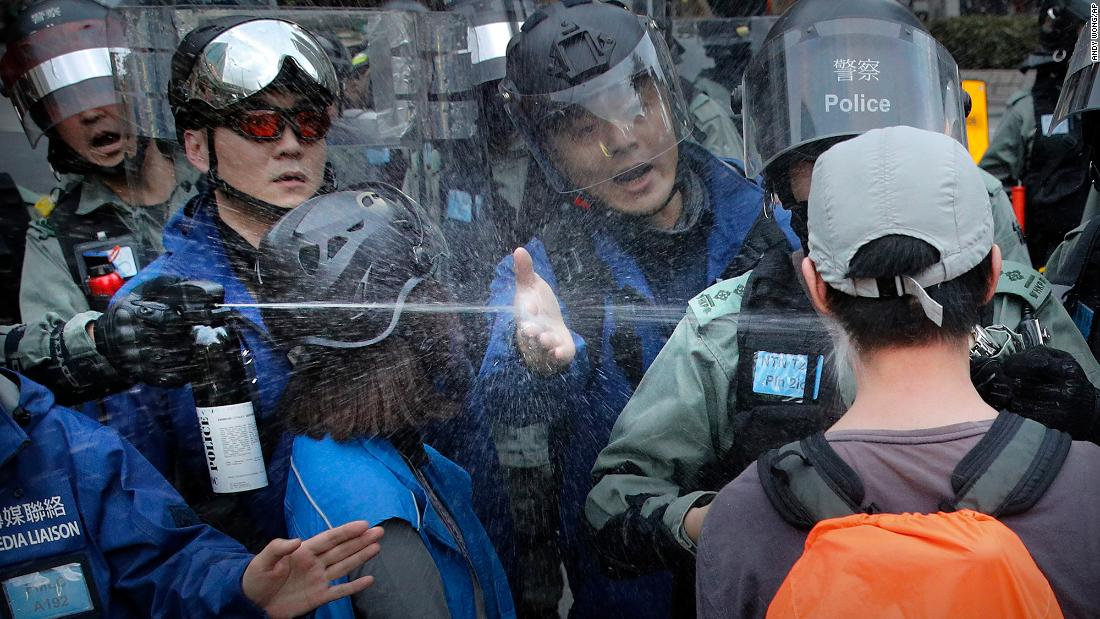 "A riot policeman sprays pepper spray at a man as they disperse a crowd during a demonstration against ""parallel traders"" who buy goods in Hong Kong to resell in mainland China on Sunday, gennaio 5."