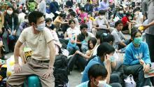 Los trabajadores migrantes con máscaras faciales esperan afuera de la estación de tren en Guangzhou, China, antes de regresar a casa durante el brote de SARS en 2003.