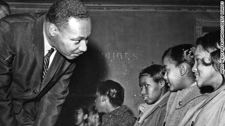 King Jr. leans over to speak to a group of students in a classroom in 1960.