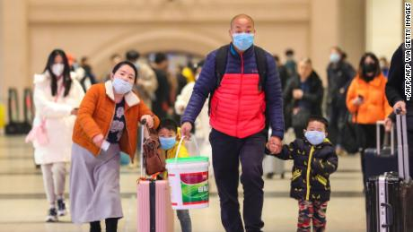 Commuters wearing face masks walk in Hankou railway station in Wuhan, where China's coronavirous outbreak first emerged last month.
