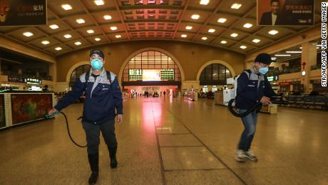 Staff members disinfect the Hankou Railway Station in Wuhan on Wednesday.