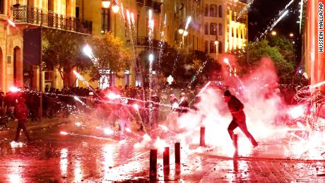 Anti-government protesters throw firecrackers at riot police during a demonstration against the new government, near Parliament Square, in Beirut, Lebanon, early Wednesday, Jan. 22, 2020.