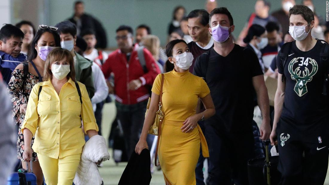Passengers wear masks as they arrive at the Ninoy Aquino International Airport in Manila, Philippines, on January 23.