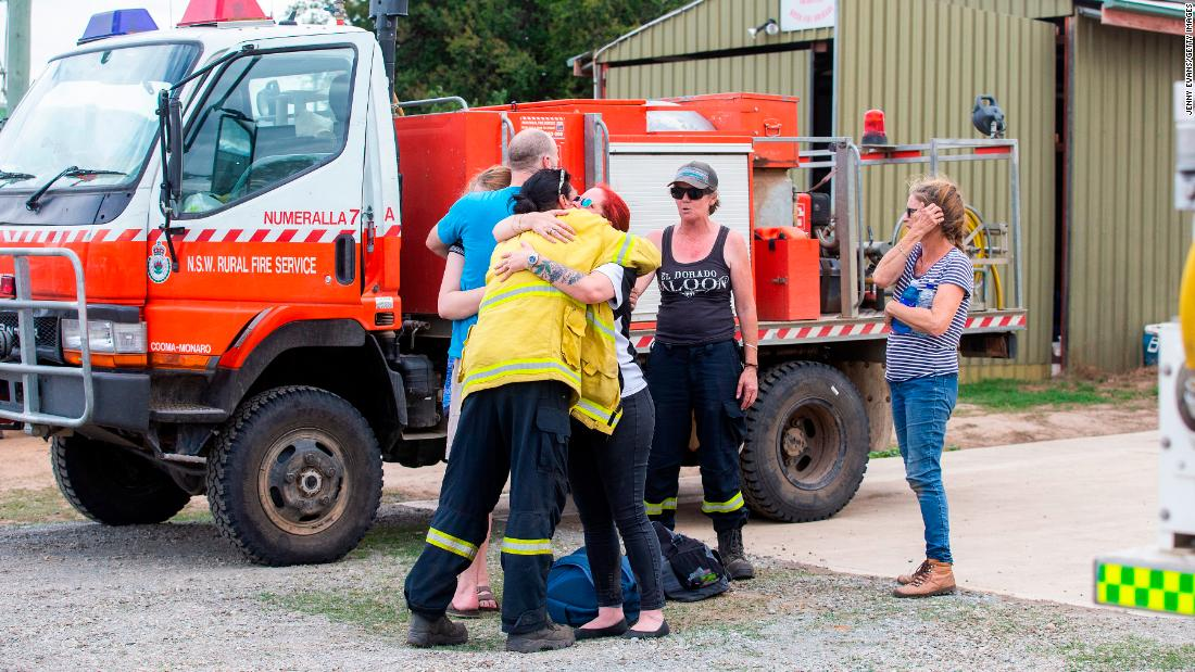 "People embrace near the scene of a <a href=""https://www.cnn.com/2020/01/23/australia/australia-firefighter-crash-intl-hnk/index.html"" 目标=""_空白&amp报价t;>water tanker plane crash</一个> in Cooma, 澳大利亚, 星期四, 一月 23. Three American crew members died in the crash."