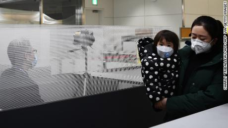 Passengers who arrived on one of the last flights from the Chinese city of Wuhan walk through a health screening station at Narita airport in Chiba prefecture, outside Tokyo, on January 23, 2020.