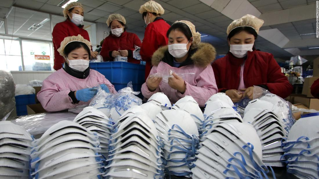 Workers manufacture protective face masks at a factory in China's Hubei Province on Thursday, January 23.