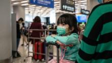 Travelers wearing face masks wait at the departure hall at West Kowloon Station on January 23, 2020 in Hong Kong.