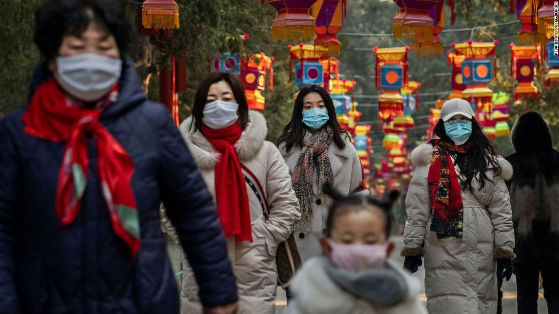 People wear protective masks as they walk under Lunar New Year decorations in Beijing on January 25.