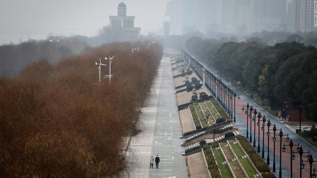 Two residents walk in an empty park in Wuhan on Monday, January 27. The city remained on lockdown for a fourth day.