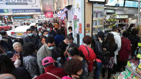 People queue for free face masks outside a cosmetics shop at Tsuen Wan in Hong Kong on January 28, 2020.