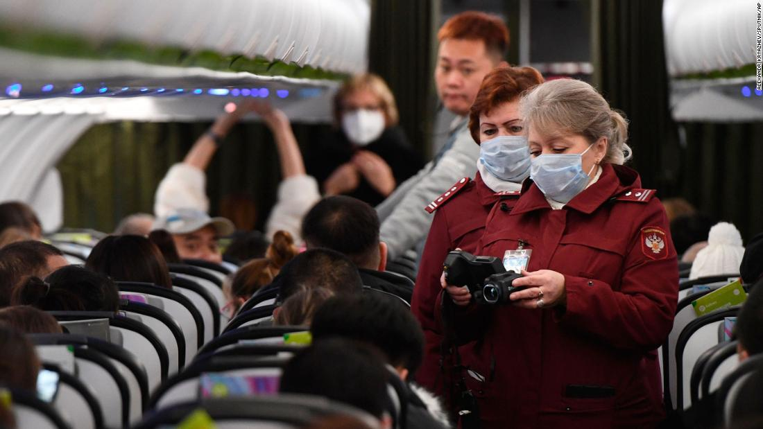 Workers at an airport in Novosibirsk, Russia, check the temperatures of passengers who arrived from Beijing on January 28.