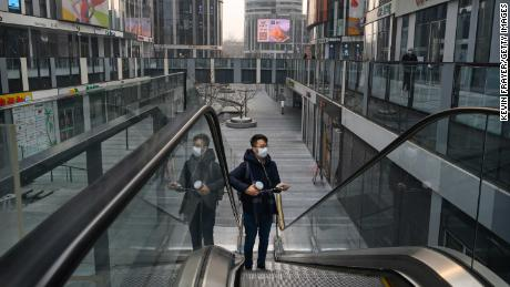 A Chinese man wears a protective mask as he rides an escalator at a large empty shopping area that would usually be busy during the Chinese New Year and Spring Festival holiday on January 28, 2020 in Beijing, China.