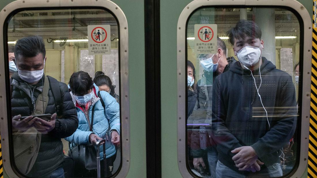 Passengers in Hong Kong wear protective masks as they wait to board a train at Lo Wu Station, near the mainland border, on January 30.