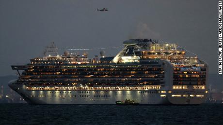 A small boat is pictured next to the Diamond Princess cruise ship as it sits anchored.