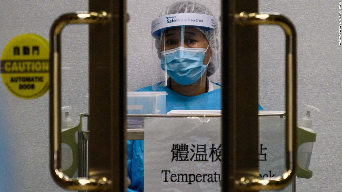 A medical worker wearing protective gear waits to take the temperature of people entering Princess Margaret Hospital in Hong Kong on February 4.