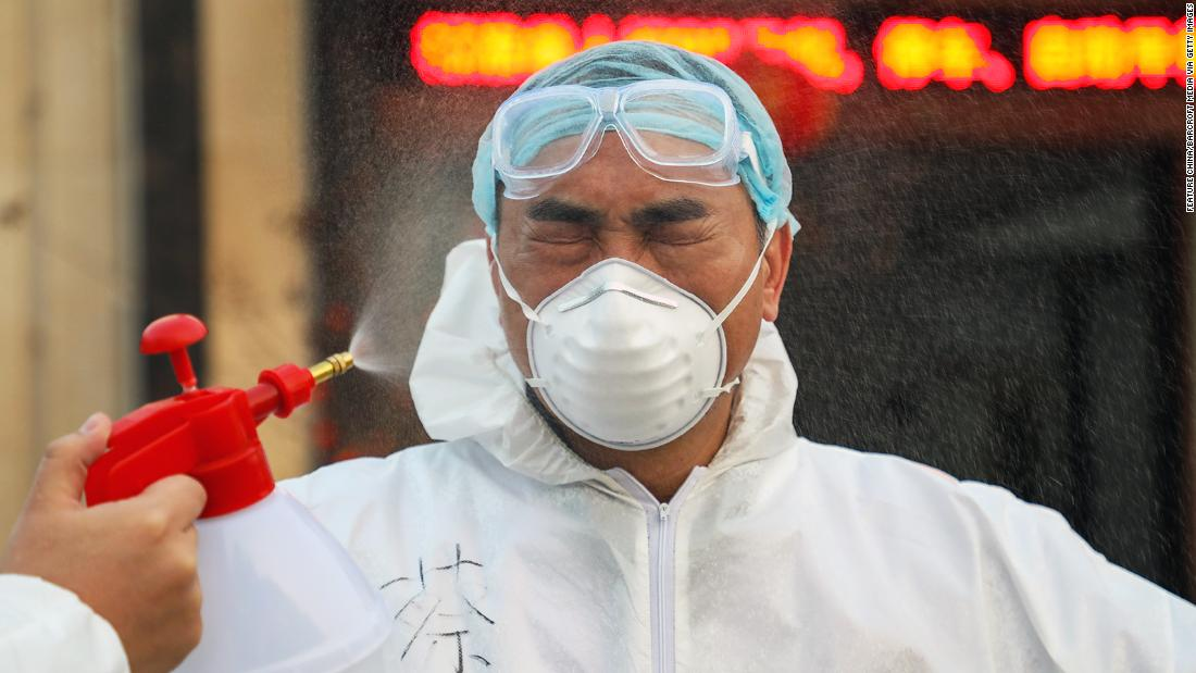 A colleague sprays disinfectant on a doctor in Wuhan on February 3.