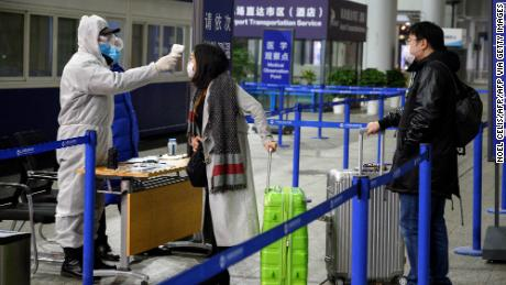 A security personnel checks the temperature of passengers arriving at the Shanghai Pudong International Airport in Shanghai on February 4, 2020. - The new coronavirus that emerged in a Chinese market at the end of last year has killed at least 425 people and spread around the world. The latest figures from China show there are more than 20,400 people infected in the country. Outside mainland China, there have been more than 150 infections reported in around two dozen places. There have also been two deaths, in the Philippines and Hong Kong. (Photo by NOEL CELIS / AFP) (Photo by NOEL CELIS/AFP via Getty Images)