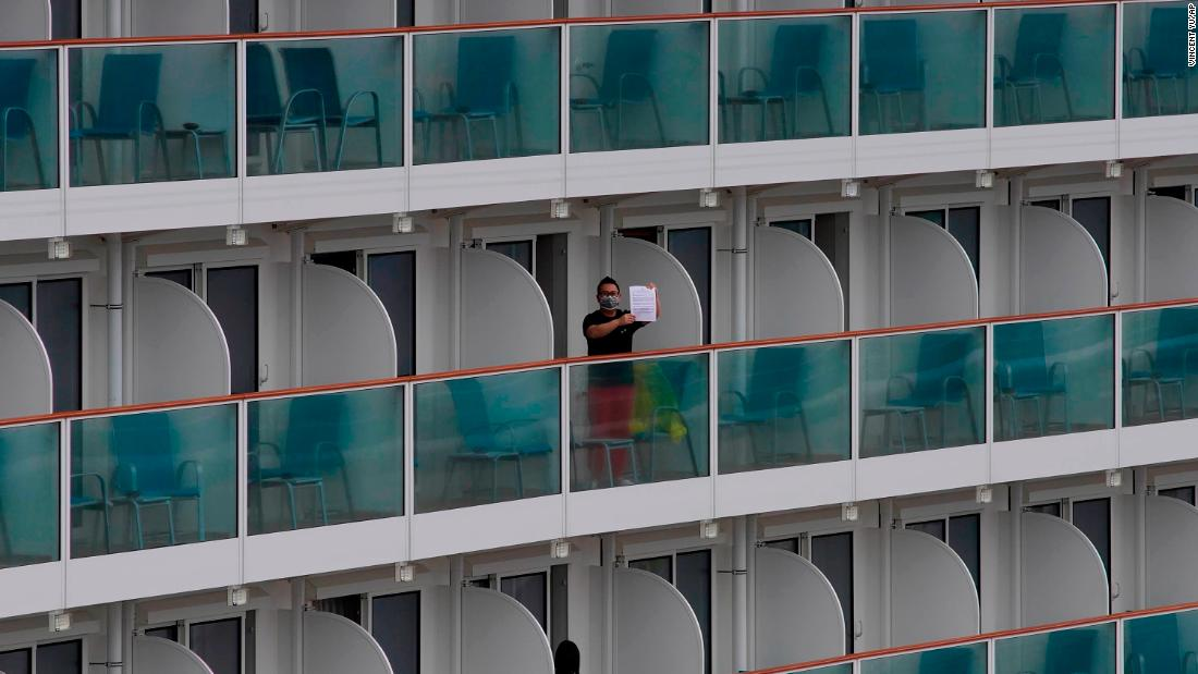 A passenger shows a note from the World Dream cruise ship docked at the Kai Tak cruise terminal in Hong Kong on Friday, February 5.