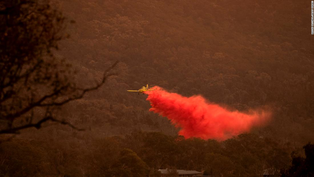 An airplane dumps fire retardant behind houses at the foot of Mount Tennent as  fire creeps through the Namadgi National Park in Canberra on Thursday, 一月 30.