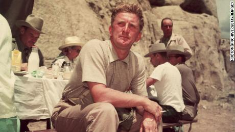 1951:  American actor Kirk Douglas sits at a picnic table on the desert location for director Billy Wilder's film, 'Ace In The Hole.'