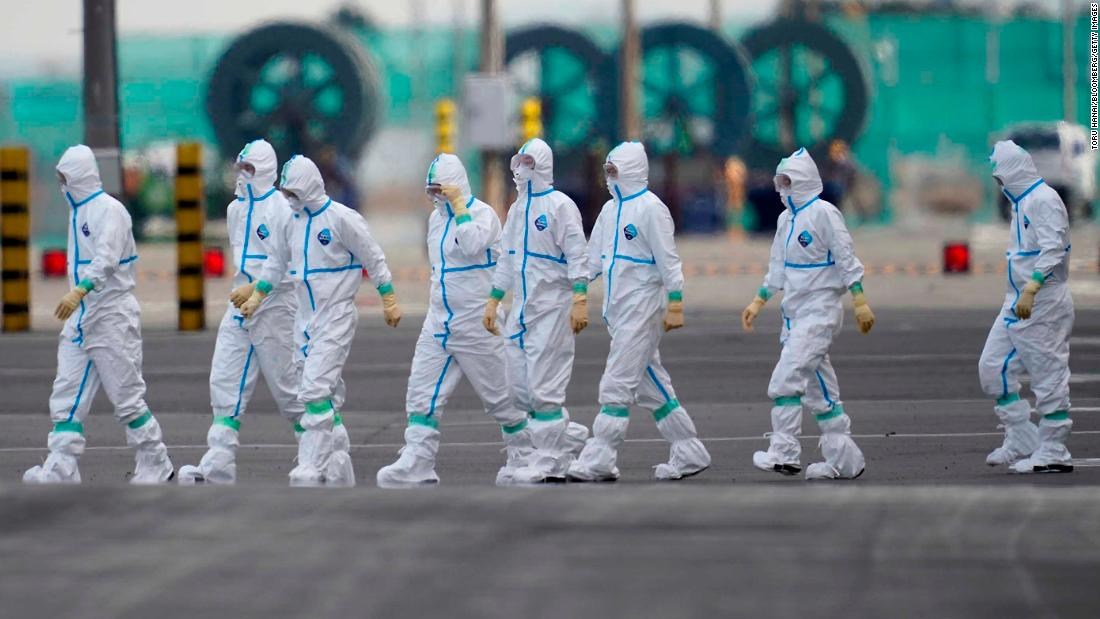 Workers in protective gear walk near the Diamond Princess cruise ship docked in Yokohama on Friday, February 7.