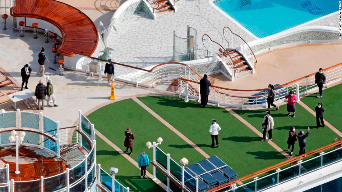 Passengers are seen on the deck of the Diamond Princess cruise ship, docked at the Yokohama Port on February 7.