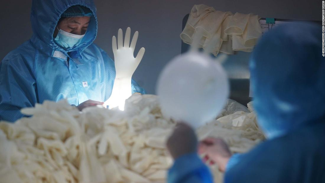 Workers check sterile medical gloves at a latex-product manufacturer in Nanjing, China, on Thursday, February 6.