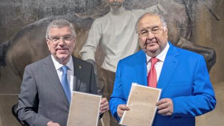 Usmanov (right) and Bach pose with a copy of the original Olympic manifesto.