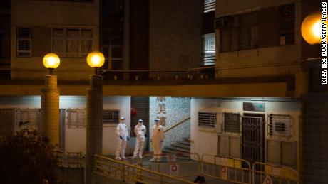 Officials wearing protective gear stand guard outside an entrance to the Hong Mei House residential building.