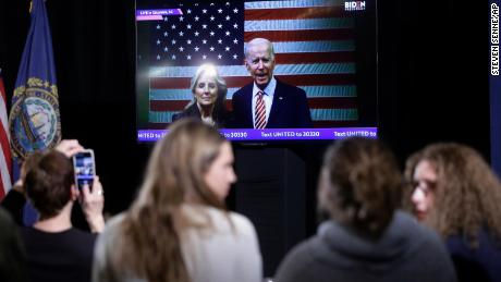 Supporters of Democratic presidential candidate former Vice President Joe Biden watch as Biden, behind right, and his wife Jill Biden, behind left, appear in a video transmission during a primary election night rally.