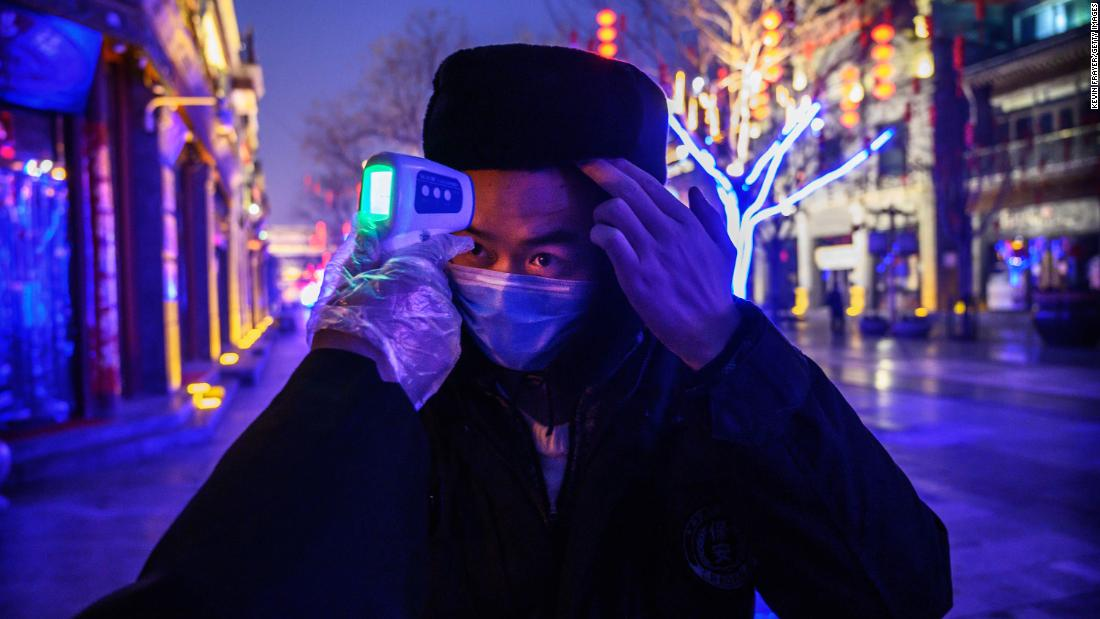 A worker has his temperature checked on a shuttered commercial street in Beijing on Wednesday, February 12.