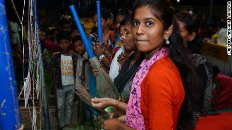 Aarti Shiv cleans an artificial cobweb meant to symbolize taboos and stigma around periods during Maasika Mahotsav in Banjara Basti, India, on May 25, 2019.