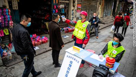 A worker taking pedestrians' body temperatures at a roadblock in Guangzhou this month.